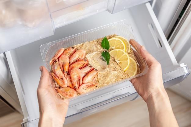 Vrouwenhanden halen een plastic bakje met rijst, garnalen en citroen uit de vriezer van de koelkast