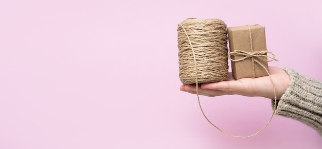 Vrouwenhanden houden een geschenk en een rol touw vast op een roze achtergrond, close-up, kopieerruimte. handgemaakte geschenken concept.
