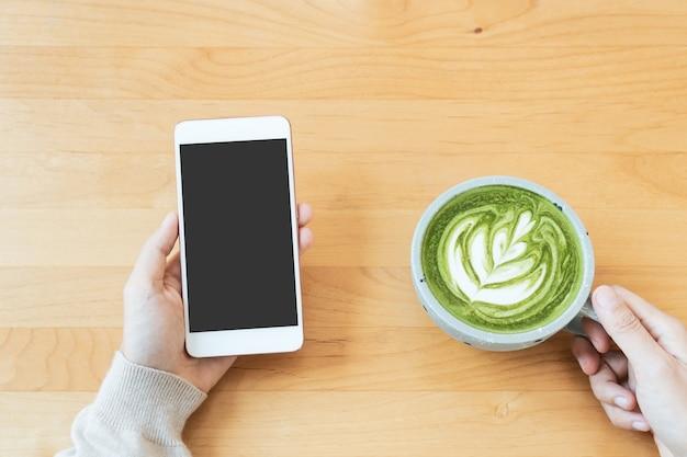 Vrouwenhanden houden een kopje groene thee latte vast tijdens het gebruik van telefoontechnologie, drank, lifestyle-concept