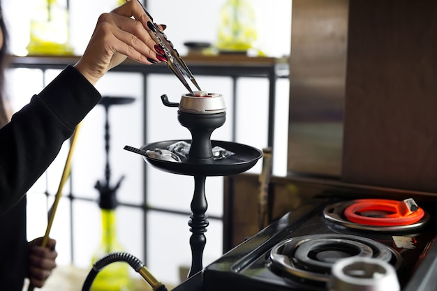 Vrouwenhanden houden een waterpijptang vast en passen de hete kolen in een metalen kom aan. zwarte waterpijp staat in een restaurant of bar.