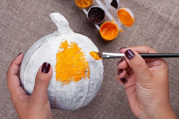 Vrouwenhanden houden een zelfgemaakte pompoen van papier-maché vast en schilderen met gouache, doe-het-zelf voor halloween op zelfisolatie.
