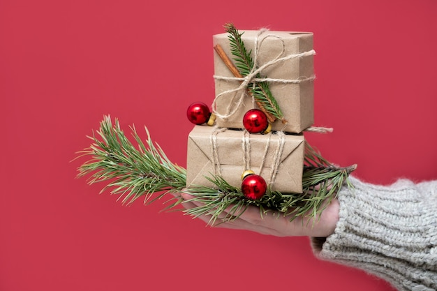 Vrouwenhanden houden geschenkdozen van kraftpapier vast met kerstdecor op een rode achtergrond, close-up. nieuwjaar achtergrond. geschenkverpakkingen van natuurlijke materialen in retro, vintage, trendstijl.