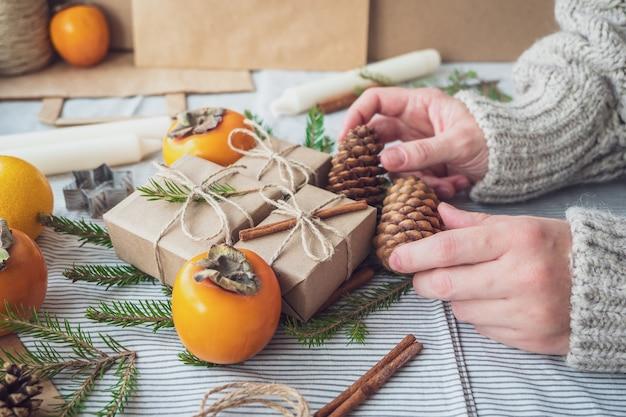 Vrouwenhanden houden geschenken vast voor het nieuwe jaar. kerst achtergrond met geschenkdozen, kegels, kerstboom en persimmon, bovenaanzicht, close-up. met de hand gemaakt cadeau.