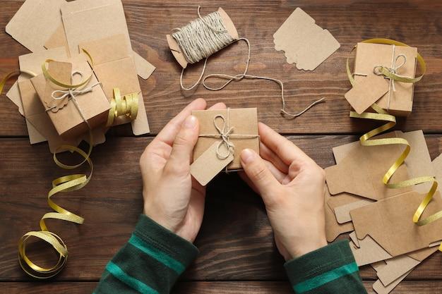 Vrouwenhanden houden handgemaakte kerstcadeaudoos met touwlint vast