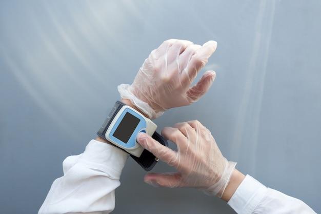 Vrouwenhanden in medische handschoenen gebruiken een bloeddrukmeter. gezondheidszorg arts concept. bespotten.