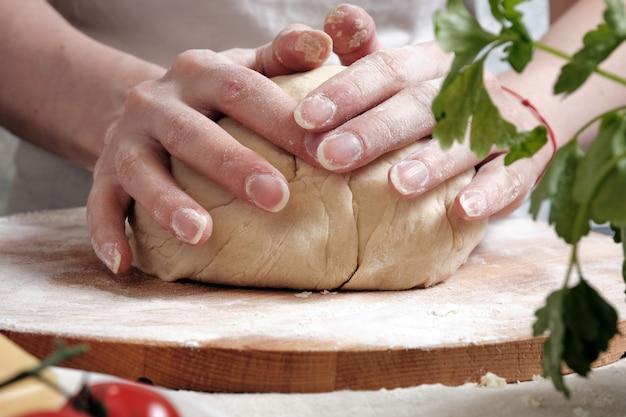 Vrouwenhanden kneden het deeg van tarwebloem