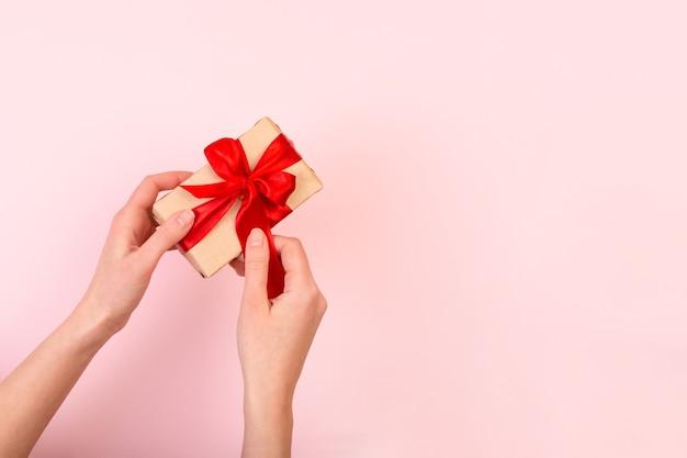 Vrouwenhanden maken het lint van de ctaft-geschenkdoos los. achtergrond met kopie ruimte voor valentijnsdag.