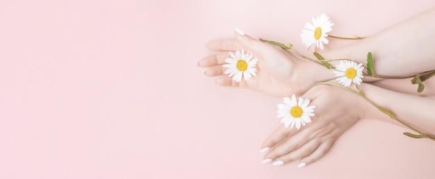 Vrouwenhanden met bloemen. natuurlijke schoonheid handcosmetica met bloemextract, product