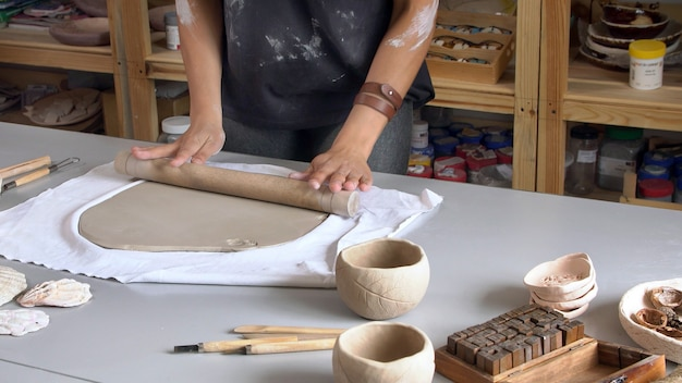 Vrouwenhanden met een deegroller rollen de klei uit voor een keramische plaat.