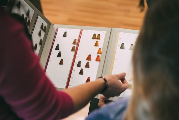 Vrouwenhanden met een kleurstofkleurencatalogus