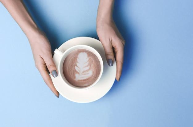 Vrouwenhanden met kop van koffie met lattekunst