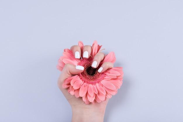 Vrouwenhanden met manicure en trouwring onder wit kant en kleine bloemen