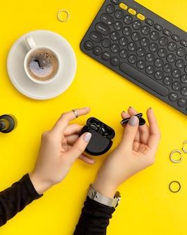 Vrouwenhanden met minimale manicure die draadloze hoofdtelefoons op geel houden