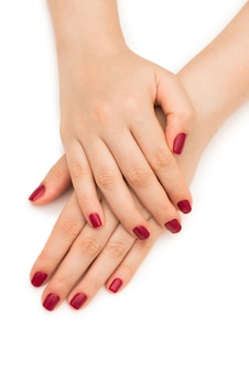 Vrouwenhanden met rode spijker die op wit wordt geïsoleerd