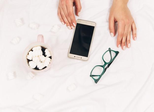Vrouwenhanden met telefoonkoffieglazen