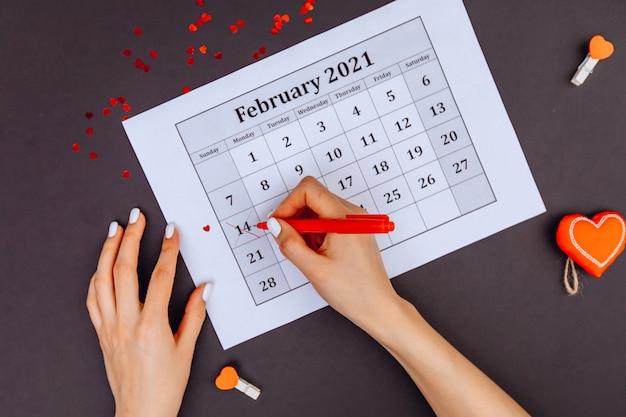 Vrouwenhanden omcirkelden het nummer 14 in de kalender met rode lippenstift. valentijnsdag.