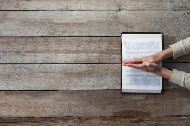 Vrouwenhanden op bijbel. ze leest en bidt over de bijbel over een houten tafel