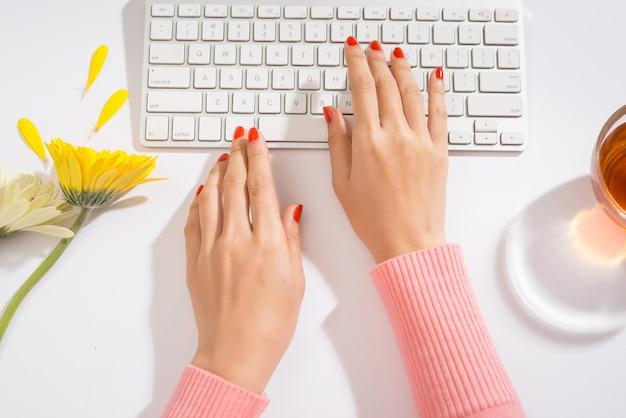 Vrouwenhanden op een computertoetsenbord close-up - typen