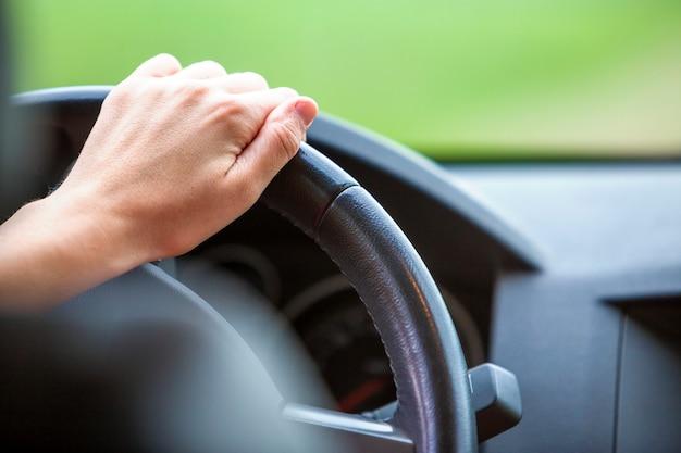 Vrouwenhanden op stuurwiel die een auto drijven.