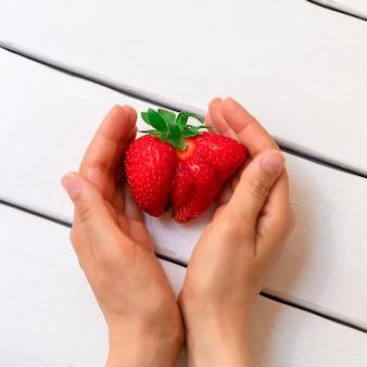 Vrouwenhanden op witte houten achtergrond die lelijke aardbei houden. lelijk eten en onvolmaakte producten