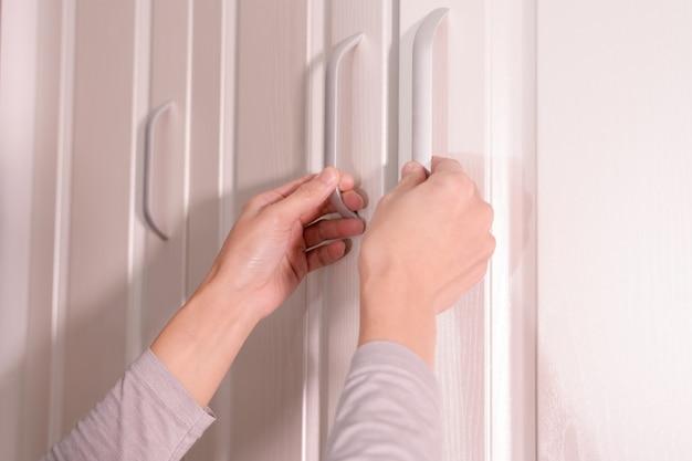 Vrouwenhanden open kast / kabinetsdeur, witte houten deur