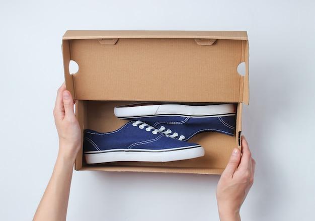 Vrouwenhanden openen een kartonnen doos met nieuwe stijlvolle sneakers op grijs. bovenaanzicht
