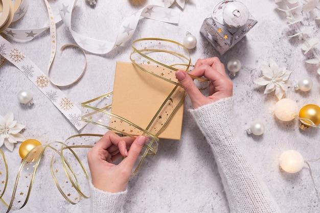 Vrouwenhanden pakken feestelijk lint op voor het inpakken van een kerstcadeau. creatieve doe-hobby.