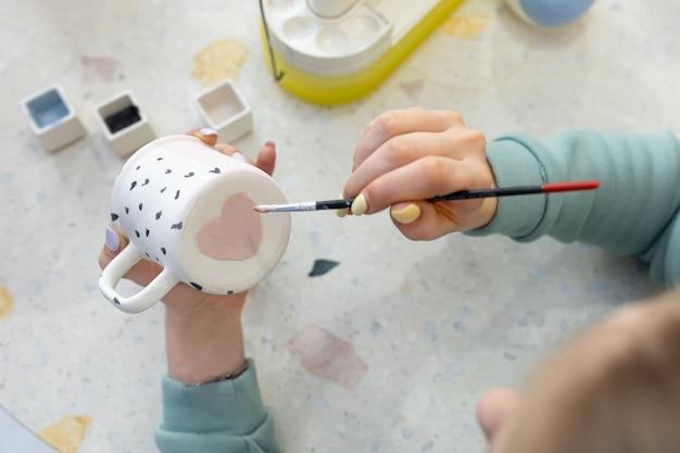 Vrouwenhanden schilderen een roze hart op de achterkant van een keramische beker