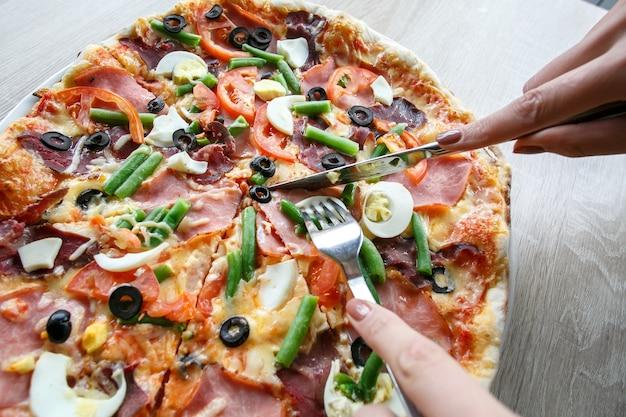 Vrouwenhanden snijden van verse pizza met bonen, kaas, ham, eieren, pepperoni en groenten. pizza snijden