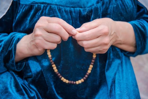Vrouwenhanden sorteren moslimparels uit gebed