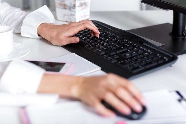 Vrouwenhanden typen op het toetsenbord van de laptop.