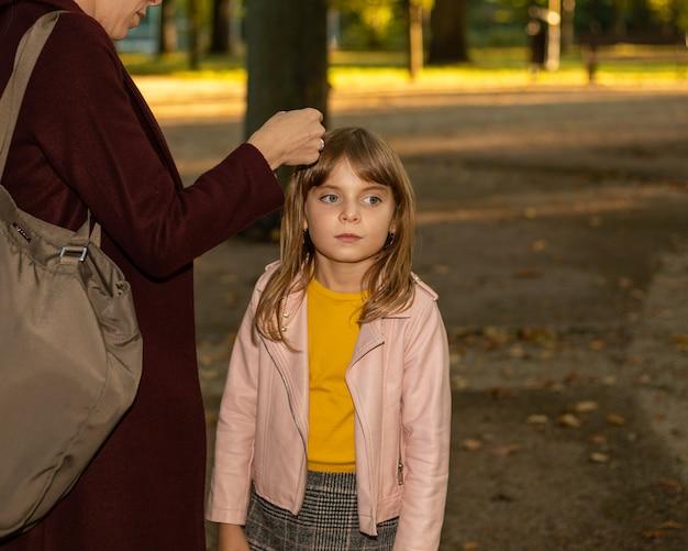 Vrouwenhanden van een moeder of verzorger maken voorzichtig een haarclip vast aan het haar van een klein meisje.