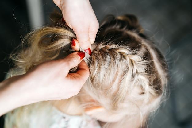 Vrouwenhanden weven vlechtjes voor een klein meisje, kinderkapsels thuis, een aartje haar.