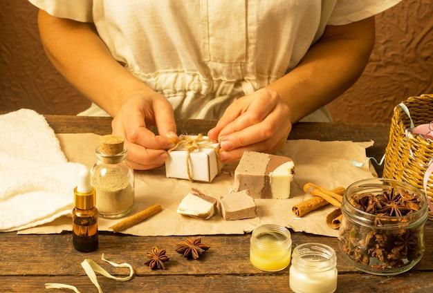 Vrouwenhanden wikkelen natuurlijke handgemaakte zeep met cacao en kaneel