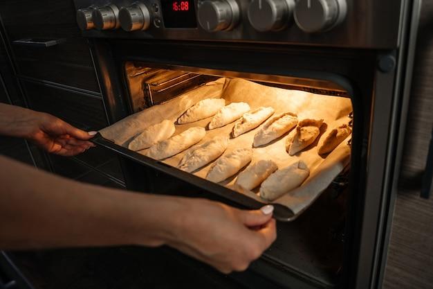 Vrouwenhanden zetten in de oven een bakplaat met rauwe gisttaarten
