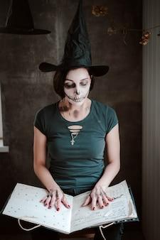 Vrouwenheksenkostuum en skeletmake-up openen een zwart spreukenboek voor een heks op halloween. verkleedpartij, tovenaar