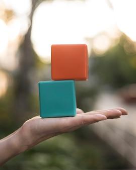 Vrouwenholding gestapelde gekleurde kubussen