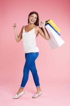 Vrouwenholding het winkelen zakken die recht geïsoleerd op roze muur kijken