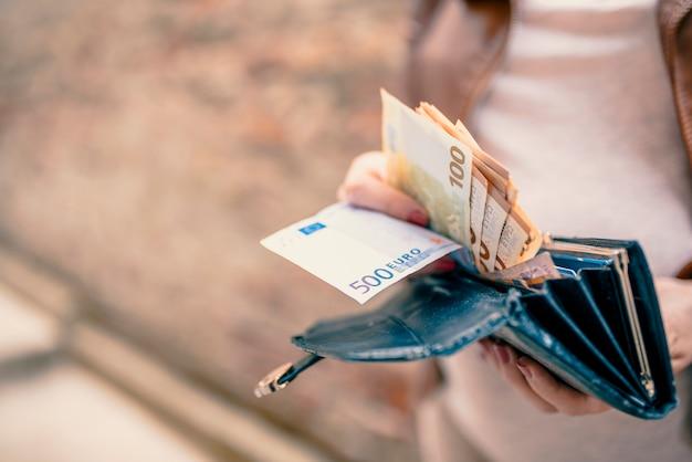 Vrouwenholding in handenportefeuille met euro geld. jonge vrouw met geld