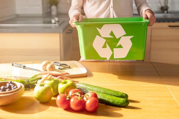 Vrouwenholding recyclingsmand in keuken