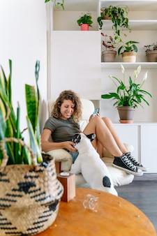 Vrouwenhondenliefhebber met buldog thuis. verticale weergave van vrouw die binnenshuis met haar hond speelt.