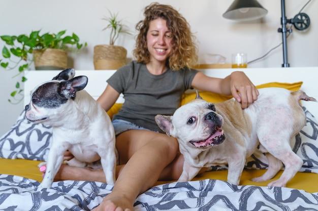 Vrouwenhondenliefhebber met buldoggen bij slaapkamer. horizontale weergave van jonge vrouw die binnenshuis met huisdier speelt