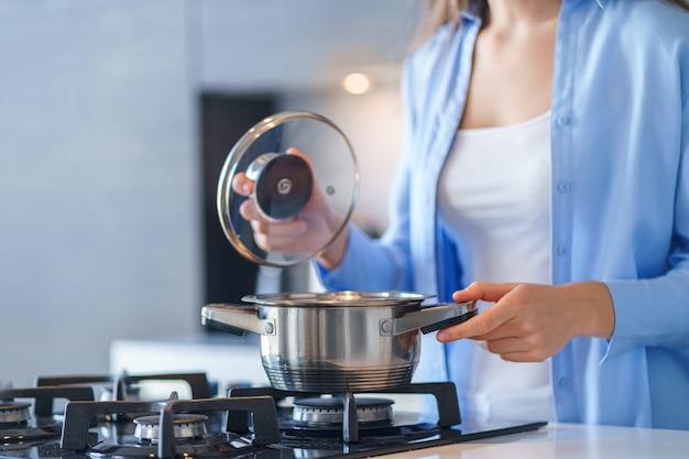 Vrouwenhuisvrouw die staal metaalsteelpan voor thuis het voorbereiden van diner in de keuken gebruiken. keukengerei om te koken