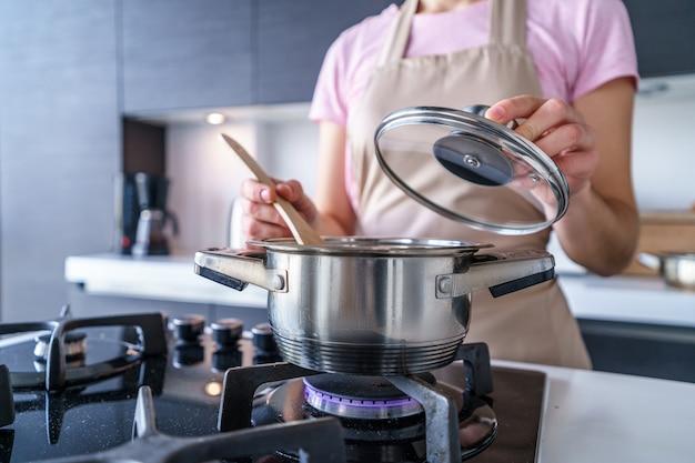 Vrouwenhuisvrouw in schort die de steelpan van het staalmetaal voor thuis het voorbereiden van diner in de keuken gebruiken.