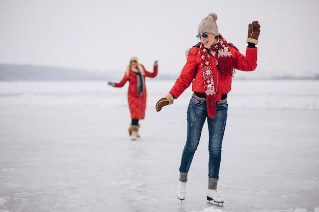 Vrouwenijs die bij het meer schaatsen