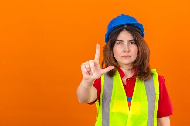 Vrouweningenieur die bouwvest dragen en veiligheidshelm die met omhoog vinger en boze uitdrukking richten die geen gebaar over geïsoleerde oranje muur tonen
