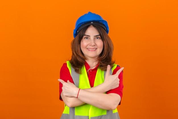 Vrouweningenieur die bouwvest dragen en veiligheidshelm die zich met gekruiste wapens bevinden die met wijsvingers aan andere kanten richten met grote glimlach op gezicht over geïsoleerde oranje backgr