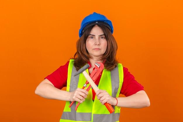 Vrouweningenieur die bouwvest en de hamer van de veiligheidshelmholding en regelbare moersleutel in handensymbool dragen van gelijkheid met mannen die zich over geïsoleerde oranje muur bevinden