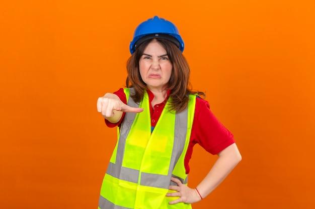 Vrouweningenieur die bouwvest en veiligheidshelm dragen die ontevreden en gefrustreerd aan de camera boos en woedend over u over geïsoleerde oranje muur richten