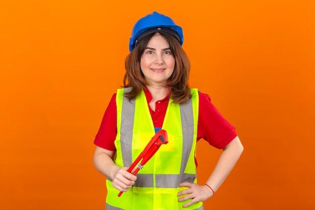 Vrouweningenieur die bouwvest en veiligheidshelm met glimlach op gezicht dragen die regelbare moersleutel in hand over geïsoleerde oranje muur houden